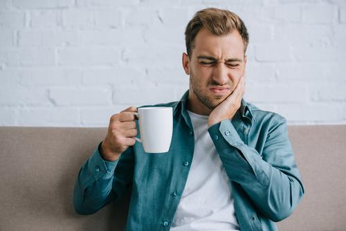 Junger Mann mit einer Tasse hält bei schmerzerfülltem Gesichtsausdruck eine Hand an die Wange (Aphthen)